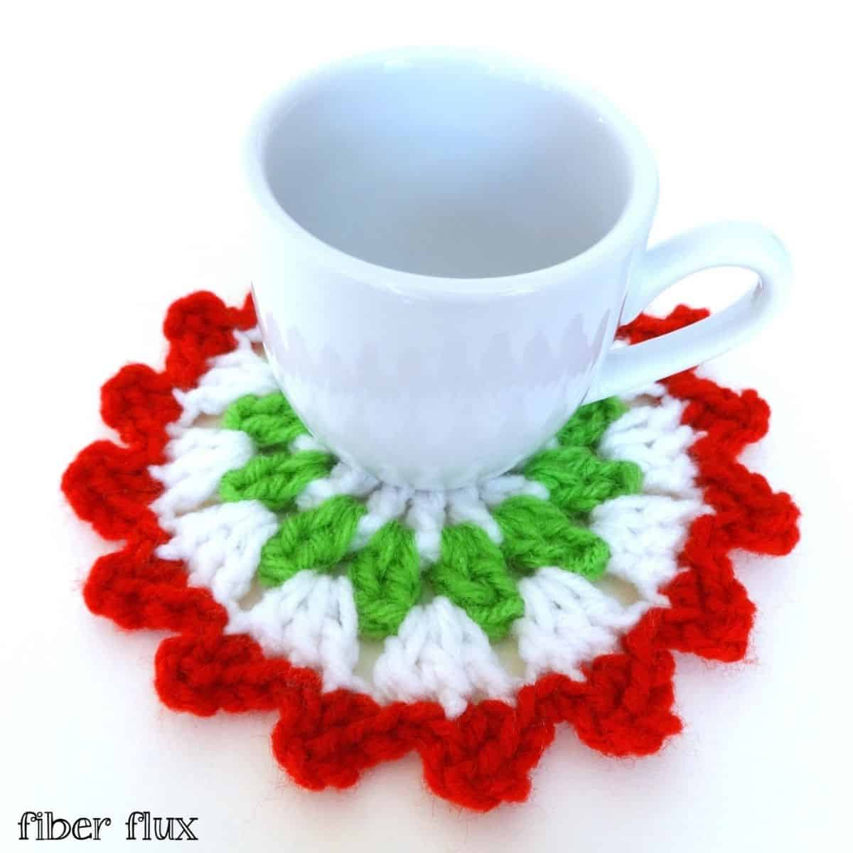 mug sitting on a white, green and red round crocheted coaster