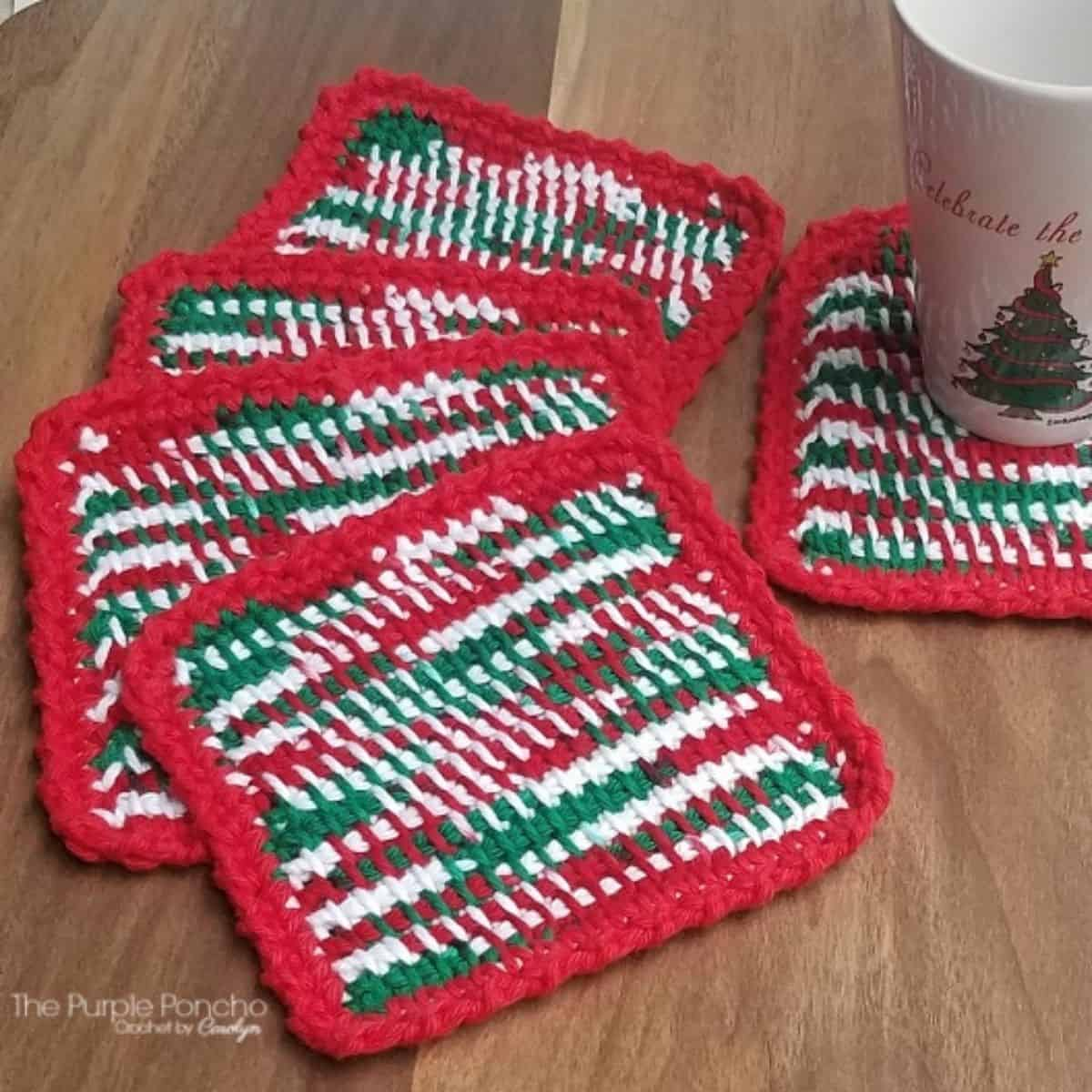 striped green red and white crochet coasters with a coffee mug on one coaster