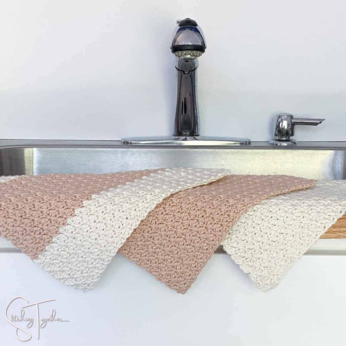 3 crochet dishcloths draped over the side of a sink