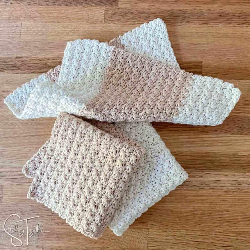 3 suzette stitch crochet washcloths on a countertop