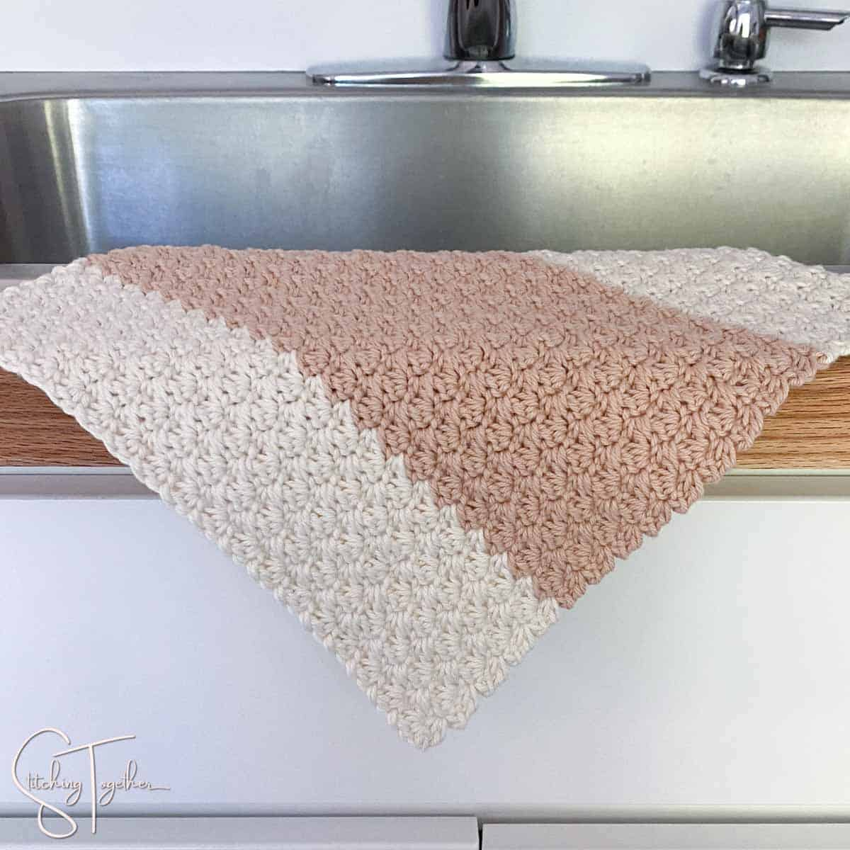one crochet dishcloth suzette stitch draped on the side of a sink
