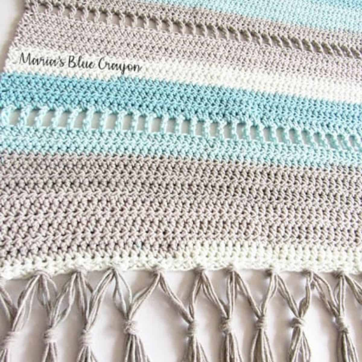 close up of gray, tan, light blue striped crochet rug with fringe