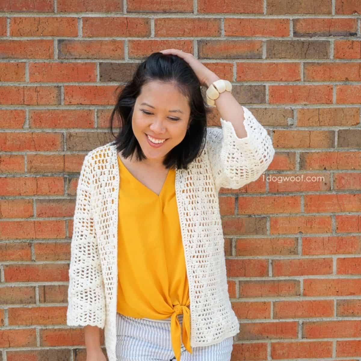 woman wearing bright yellow shirt and crocheted cardigan