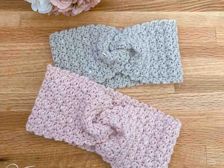 two twist crochet ear warmers laying flat next to a bouquet of roses